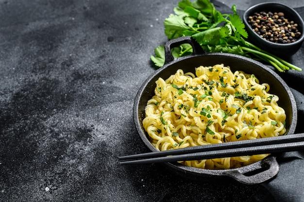 Noodles istantanei con coriandolo in una pentola di ghisa. .