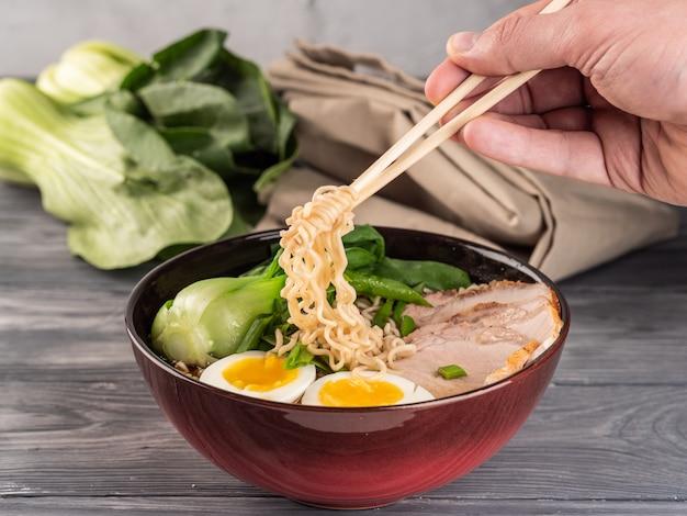 Noodles istantanei con fettine di maiale e cavolo cinese.