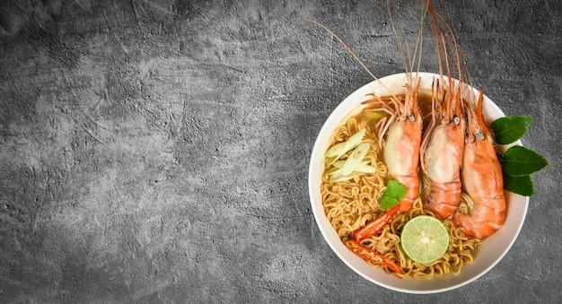Noodles istantanei con scodella di gamberi speziati lime / frutti di mare cotti con zuppa di gamberi tavolo da pranzo e spezie ingredienti cibo tailandese tradizionale asiatico