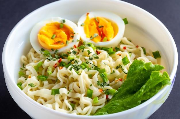 Noodles istantanei con verdure e uovo nel piatto. ciotola di tagliatelle su bianco
