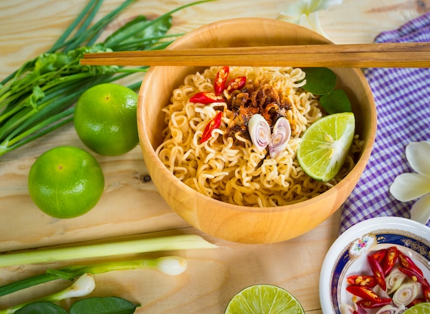 Noodles istantanei in ciotola di legno e contorni di verdure