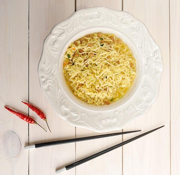 Noodles istantanei in una ciotola con le bacchette