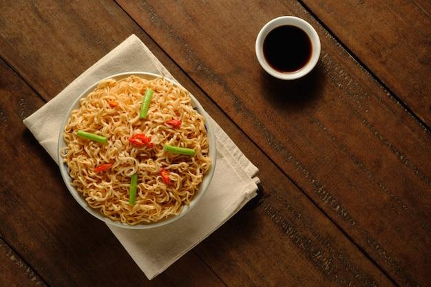 Noodles istantanei in una ciotola con un panno posto su un tavolo di legno