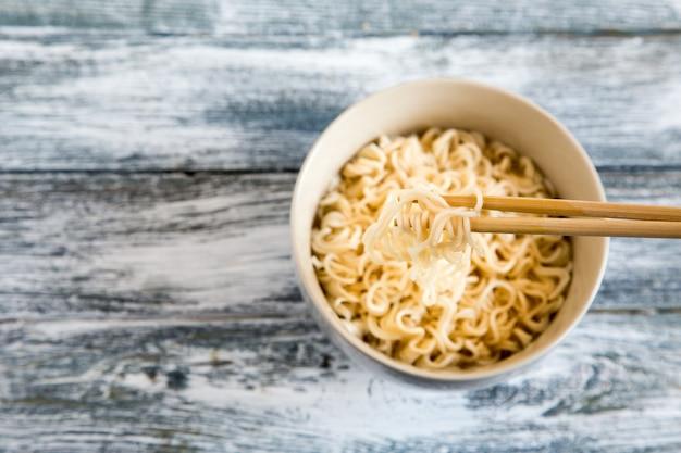 Noodles istantanei su fondo in legno. tagliatelle istantanee cinesi cotte.