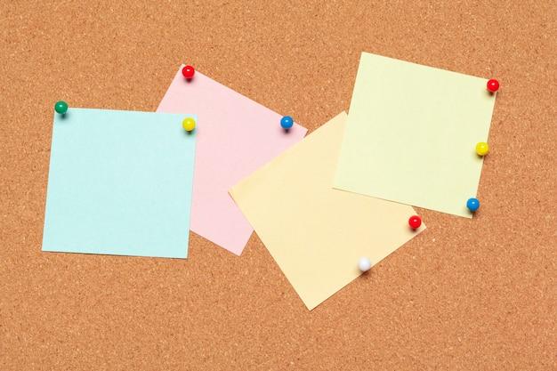Nota adesiva appuntata sulla bacheca di sughero con puntine da disegno