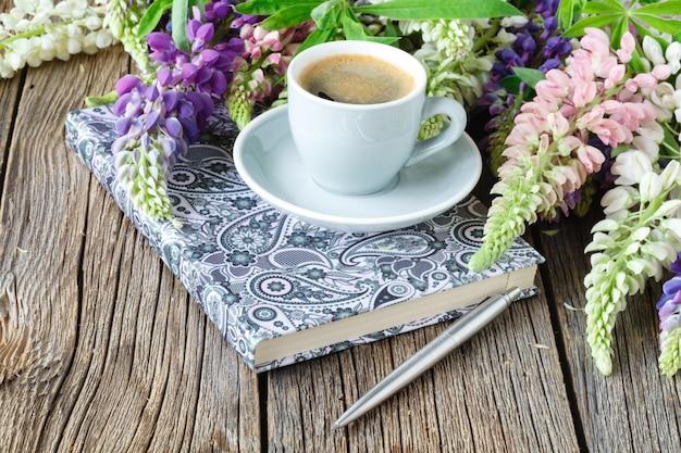 Nota con una penna e una tazza di caffè, fiori di lupini sul tavolo di legno