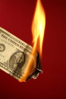 Nota del dollaro che brucia nel fuoco sul rosso