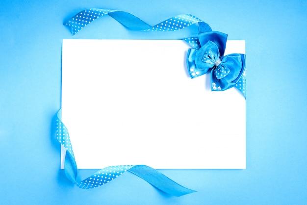 Nota di carta bianca con nastri blu a pois e fiocco su sfondo blu.