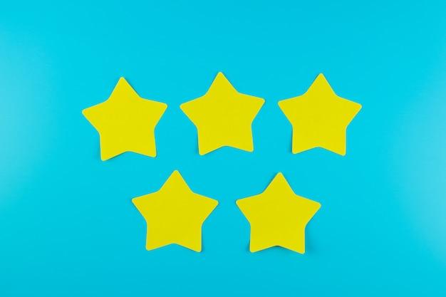 Nota di carta gialla a cinque stelle su fondo blu con lo spazio della copia per testo. recensioni dei clienti, feedback, valutazione, classificazione e concetto di servizio.