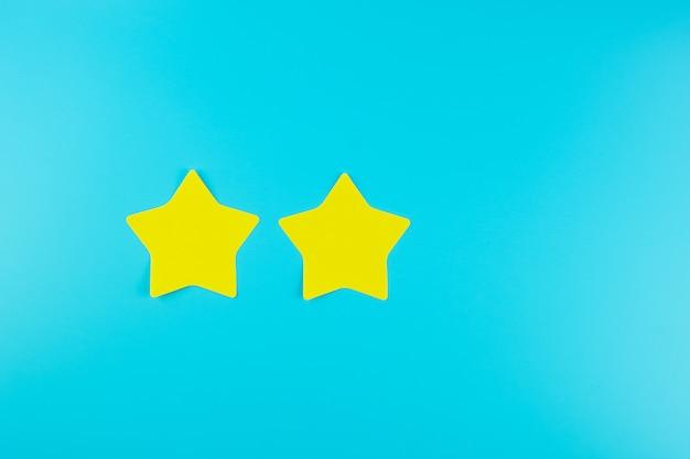 Nota di carta gialla a due stelle su fondo blu con lo spazio della copia per testo. recensioni dei clienti, feedback, valutazione, classificazione e concetto di servizio.