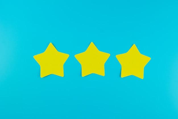 Nota di carta gialla a tre stelle su fondo blu con lo spazio della copia per testo. recensioni dei clienti, feedback, valutazione, classificazione e concetto di servizio.