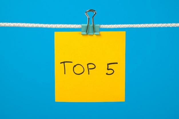 Nota di carta gialla su stendibiancheria con testo top 5