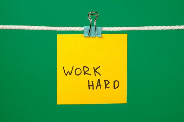 Nota di carta gialla sulla corda con testo work hard