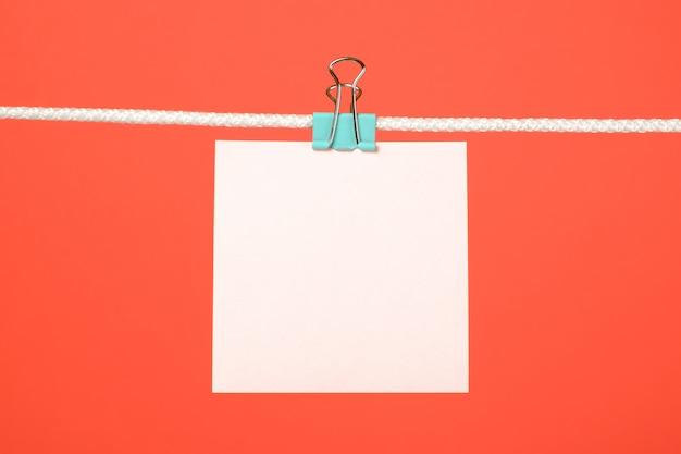 Nota di carta rosa in bianco sulla corda da bucato