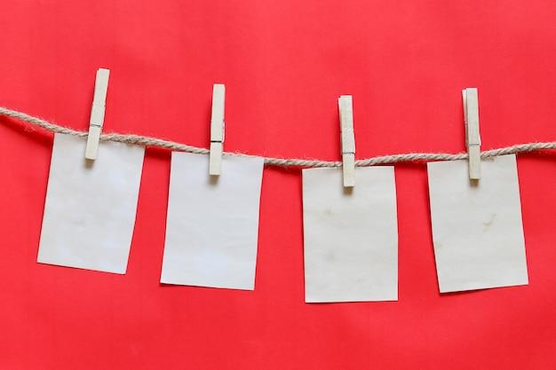 Nota marrone vuota su clothesline e sfondo rosso.