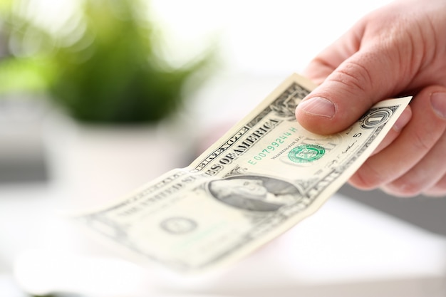 Nota maschio del dollaro americano della carta della tenuta della mano dell'uomo d'affari