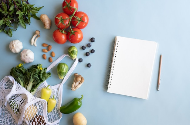 Nota per l'alimentazione, verdura e frutta nella borsa ecologica. ricetta del pasto vegano sulla superficie blu.