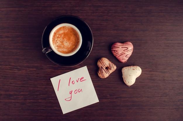 Nota ti amo con una tazza di caffè e biscotti