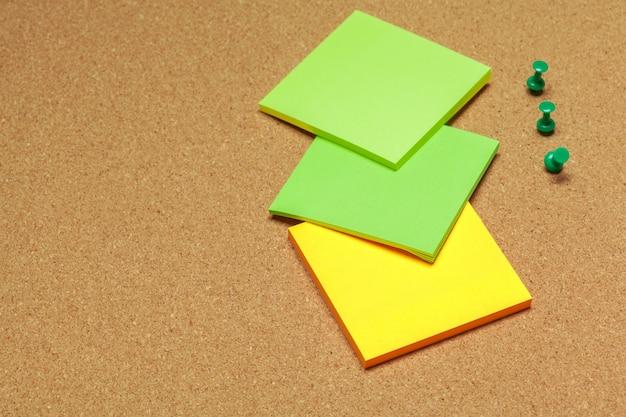 Note adesive colorate con simboli sulla superficie del sughero