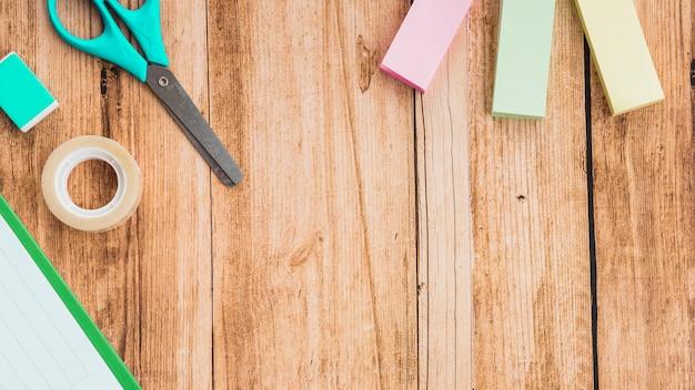 Note adesive; forbice; nastro e gomma sul tavolo di legno