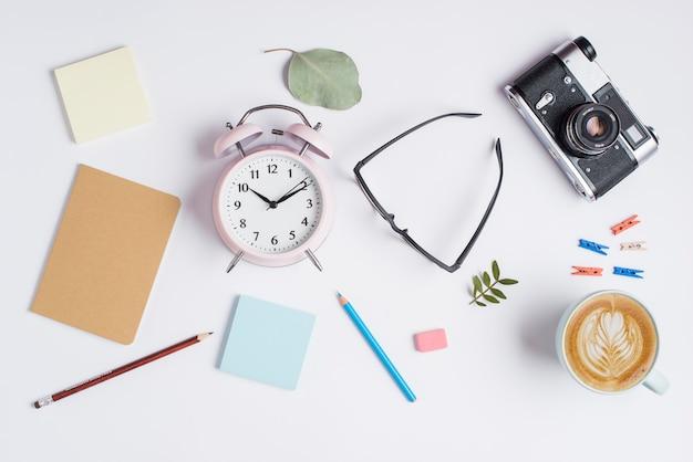 Note adesive; matite; gomma da cancellare; occhiali; macchina fotografica e tazza del cappuccino con arte del latte su fondo bianco