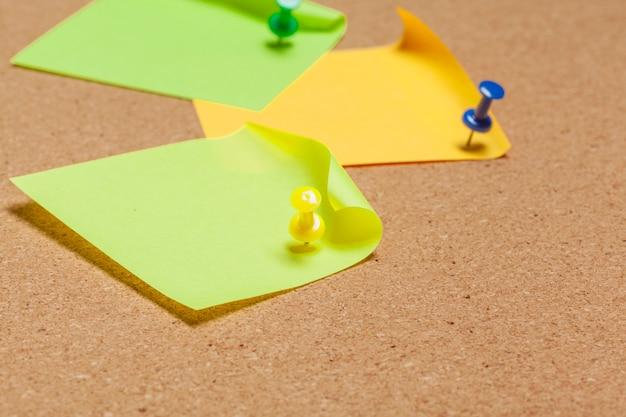 Note appiccicose appuntate sulla bacheca di sughero con puntine da disegno