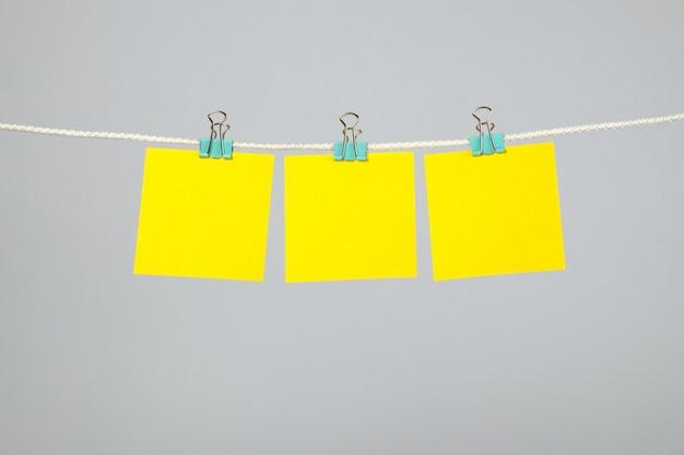 Note di carta gialle in bianco che appendono sulla corda da bucato