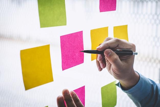Note di post-it di uso dell'uomo d'affari all'idea di pianificazione e alla strategia di marketing aziendale, nota appiccicosa sulla parete di vetro