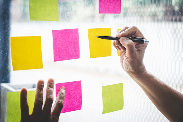 Note di post-it di uso dell'uomo d'affari all'idea di pianificazione e alla strategia di marketing di affari, nota appiccicosa sulla parete