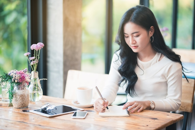 Note di scrittura della giovane donna dell'asia al caffè