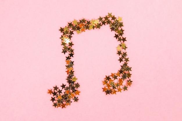 Note musicali di coriandoli dorati stellati che giace su uno sfondo pastello rosa.