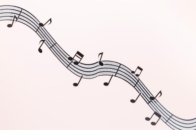Note musicali ondulate distese piatte con sfondo rosa