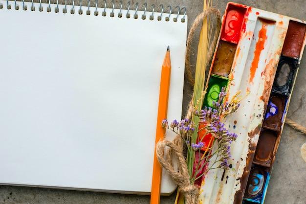 Noteboo con acquerelli, fiori e una matita