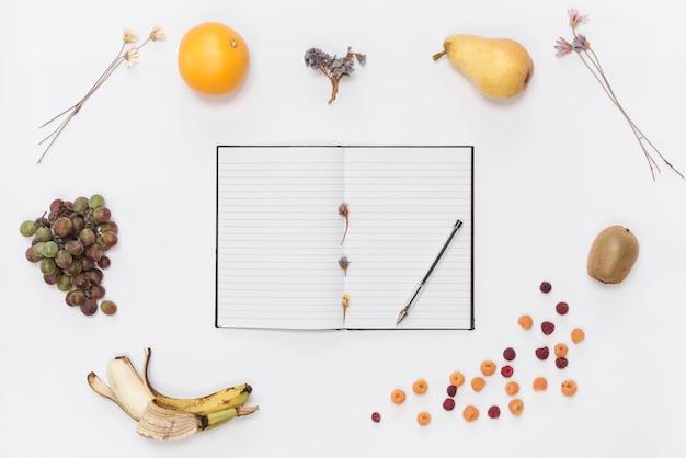 Notebook a linea singola con notebook; penna; croissant; frutta; caffè e fiori secchi su sfondo bianco
