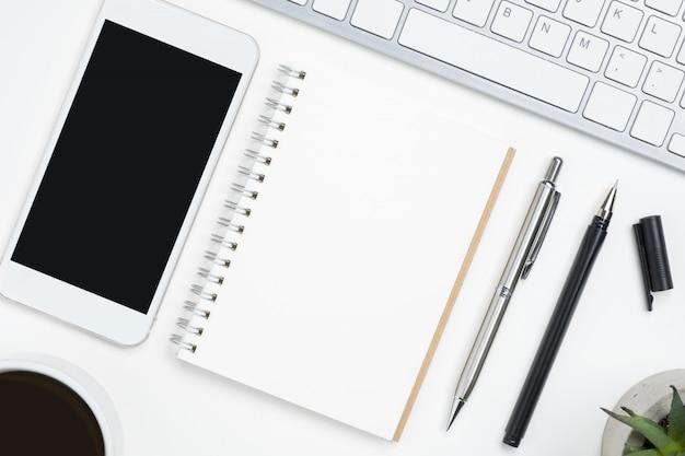 Notebook bianco e cellulare con schermo mockup vuoto sono in cima al tavolo scrivania bianca.
