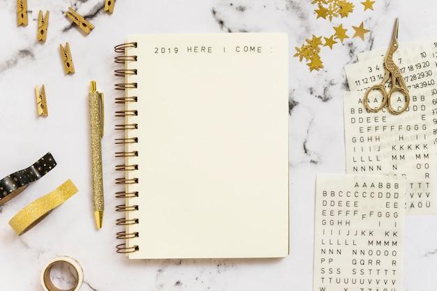 Notebook con 2019 qui vengo iscrizione vicino serie di articoli di cancelleria