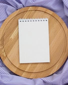 Notebook con copertina vuota e tagliere circolare su una tovaglia a righe viola, vista dall'alto.