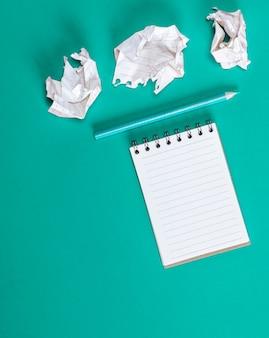 Notebook con fogli bianchi vuoti, fogli di carta accartocciati
