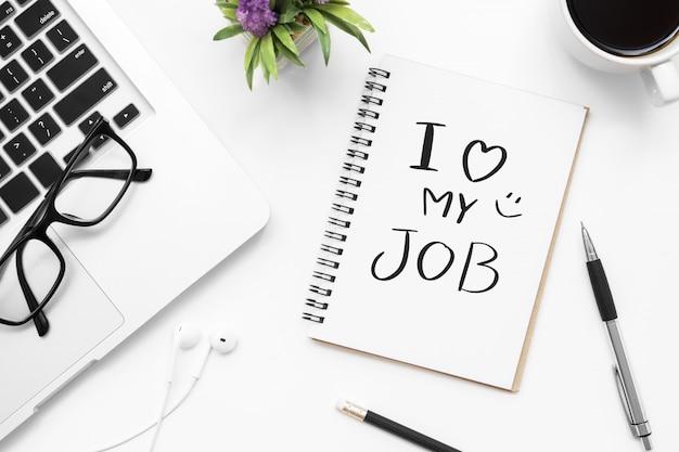 Notebook con i love my job text è sul tavolo da ufficio bianco con forniture.