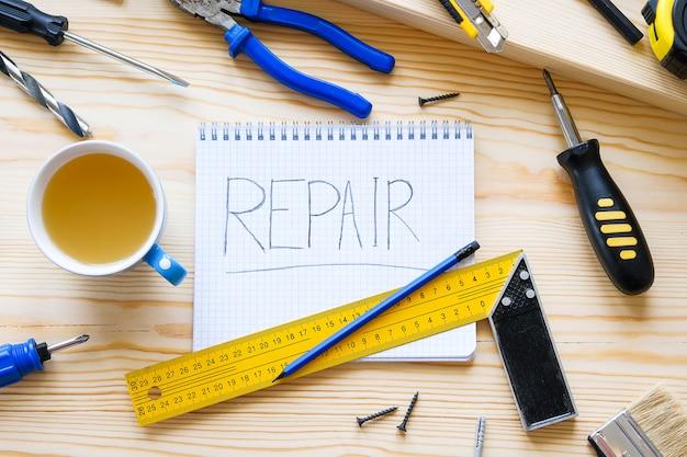 Notebook con la riparazione di parole, una tazza di tè e strumenti per la costruzione di una casa o di un appartamento di riparazione.