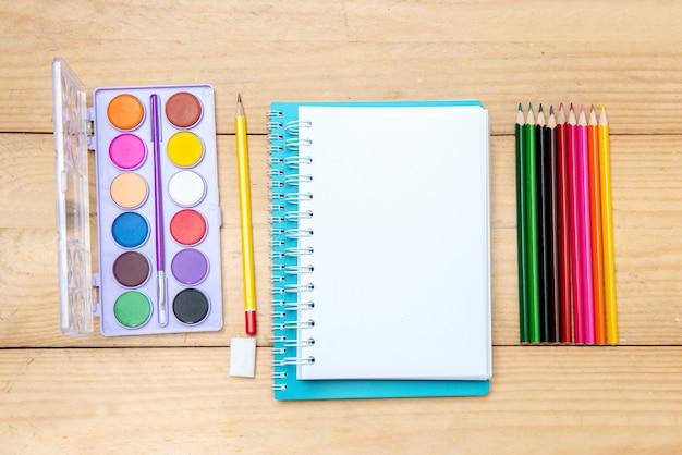 Notebook con materiale scolastico e cancelleria sul tavolo di legno