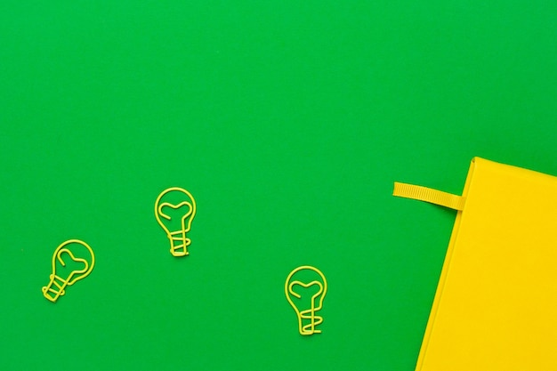 Notebook con pagine bianche e idea di lampadina paperclip sul verde