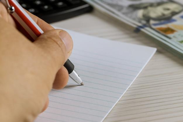 Notebook con pagine bianche su una penna e dollari americani