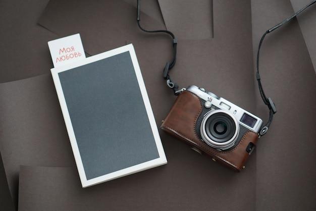 Notebook con penna e fotocamera su sfondo bianco vista dall'alto.