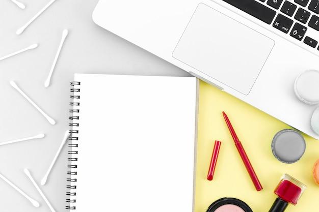 Notebook con vista dall'alto con trucco e cotton fioc