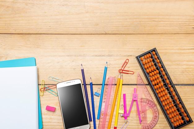 Notebook e cellulare con materiale scolastico e cancelleria sul tavolo di legno