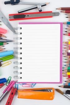 Notebook e strumenti di scuola o ufficio su sfondo bianco