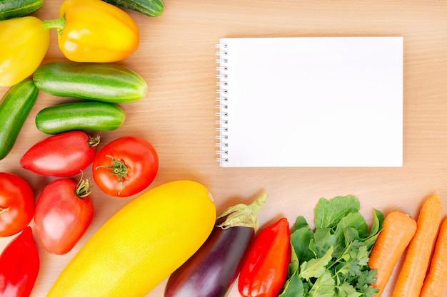 Notebook e verdure fresche sul tavolo.