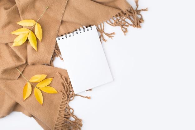 Notebook, foglie di autunno, plaid su sfondo bianco.