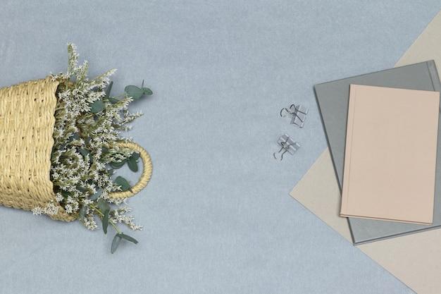 Notebook grigio e graffette, carta e note rosa, cestino di paglia con fiori bianchi e rami di eucalipto